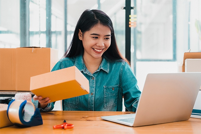 woman working at computer with boxes shipping