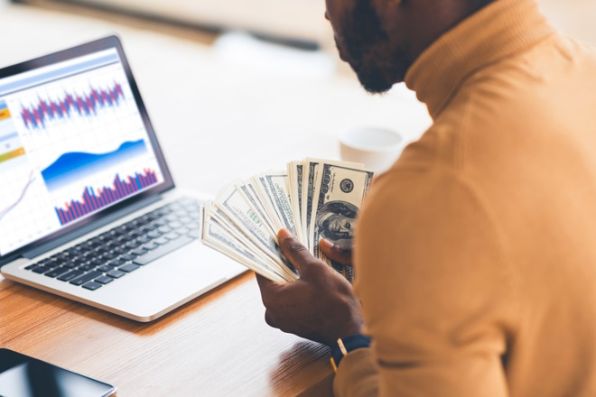 man holding cash looking at spreadsheet