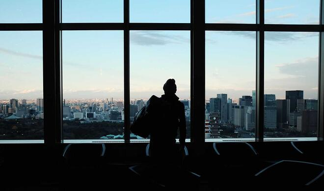 man standing with pack in front of city skyline