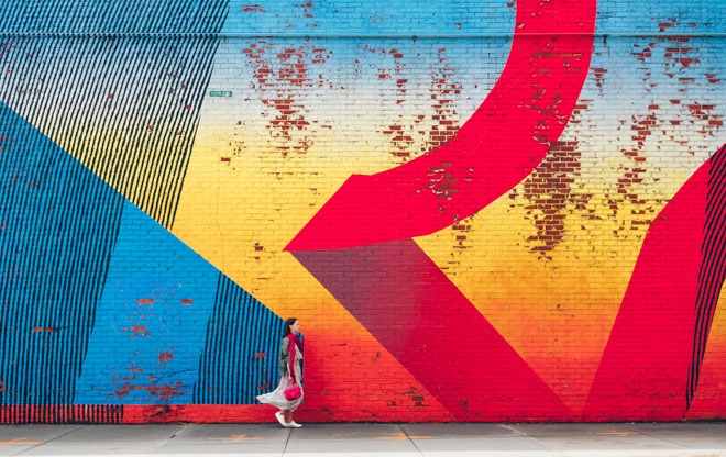 woman standing in front of street mural