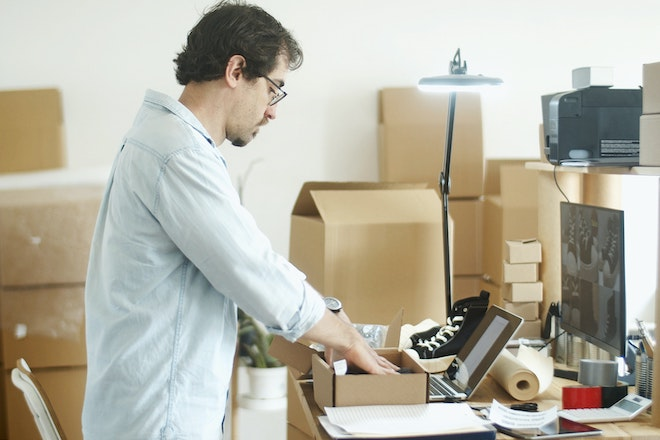 man putting items into boxes
