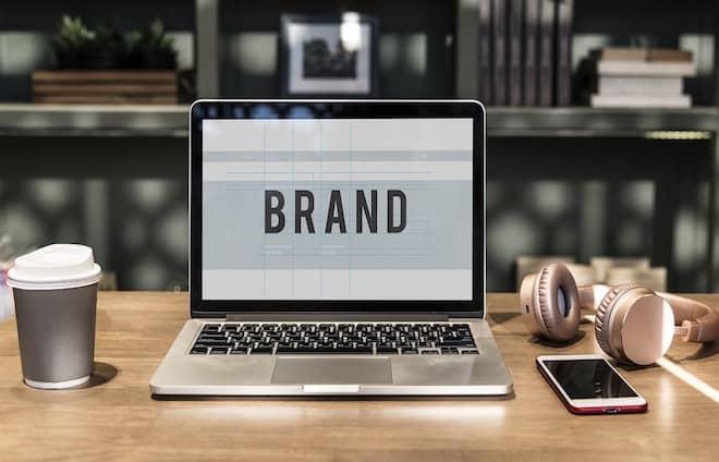 laptop on desk saying brand