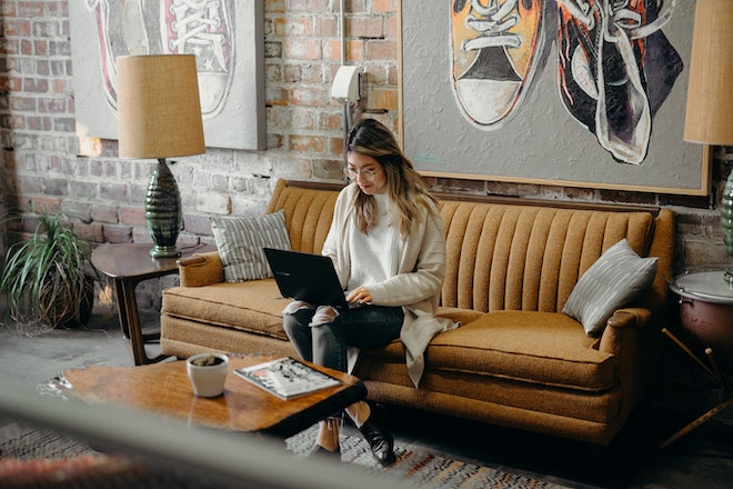 business owner working from laptop on couch