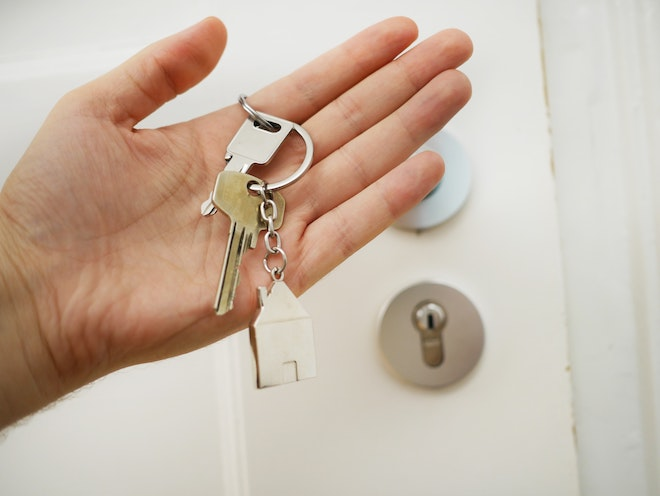 hand holding house keys in front of rental property