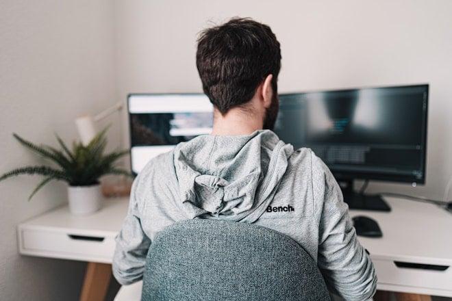 man in gray hoodie sitting at desk