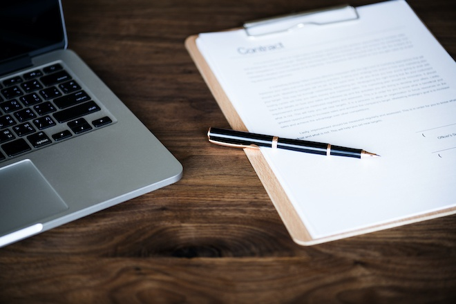 business contract next to laptop