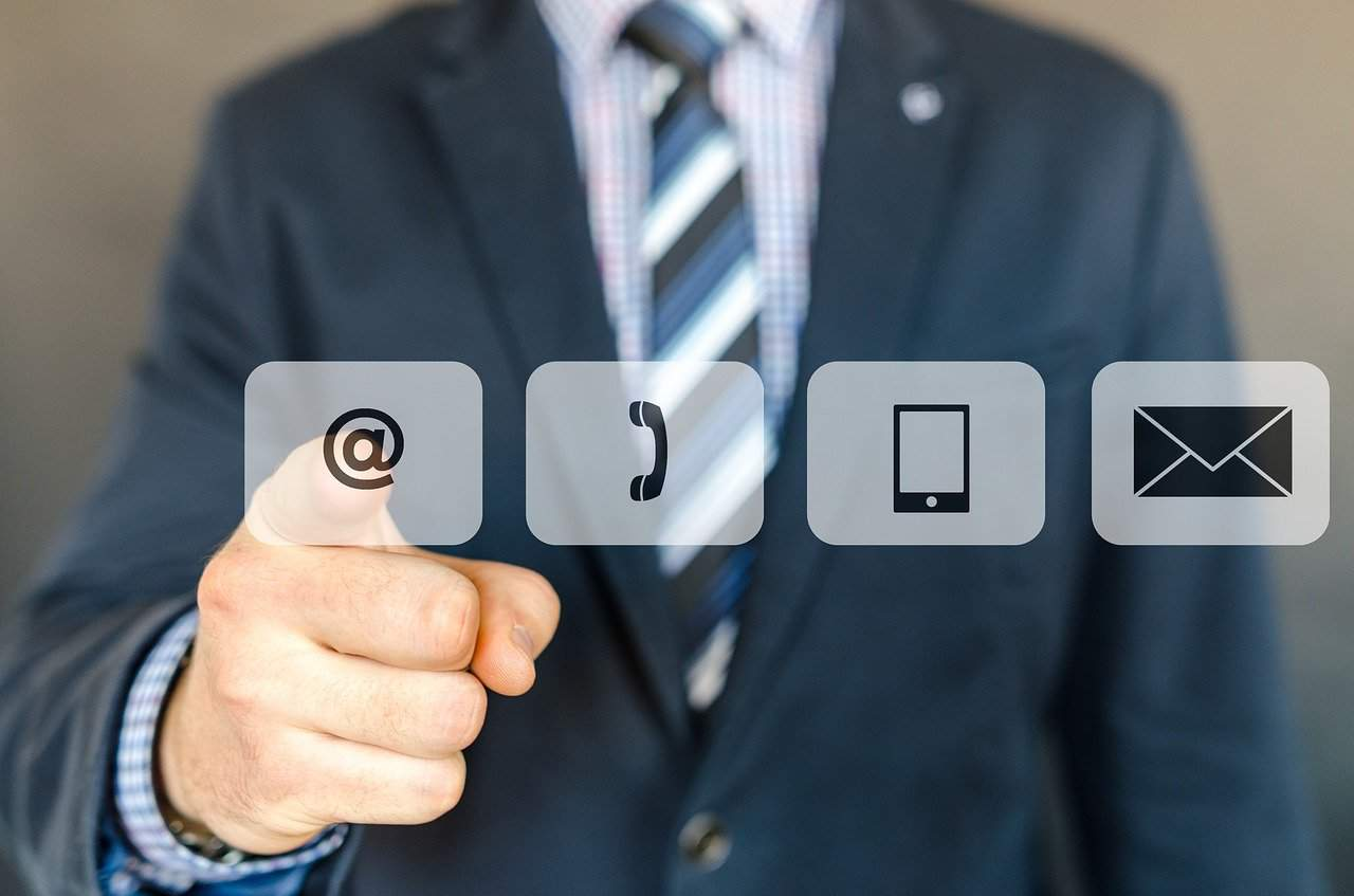 man in suit pointing at email icon