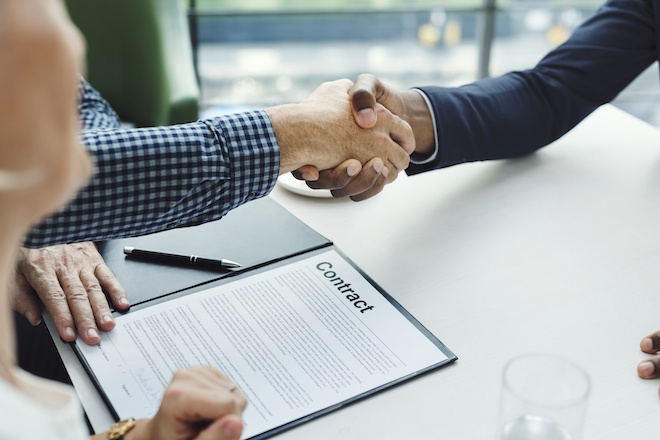 Two men shaking hands over consulting contract
