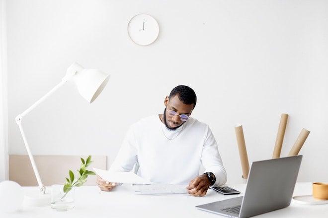 man looking at paperwork at desk