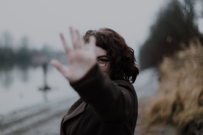 woman standing outside with hand help up in front of face