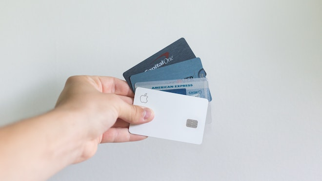 A person holding credit cards against a white background wall