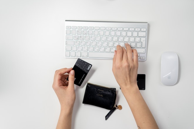 person typing credit card info on keyboard