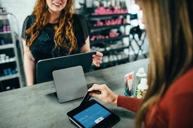 shopper checking out at credit card reader