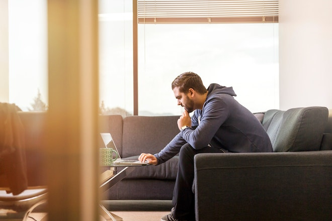 man working on laptop from couch