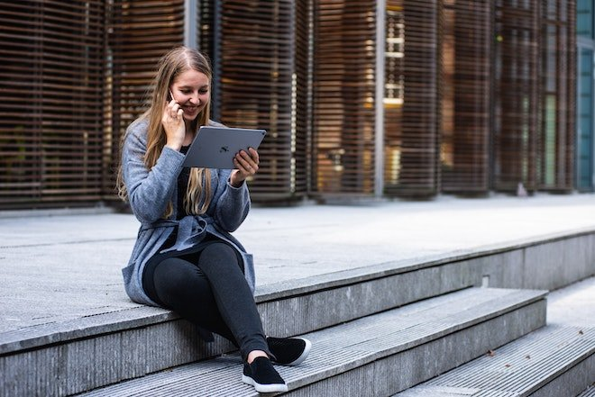 woman sitting outside on steps with phone and tablet
