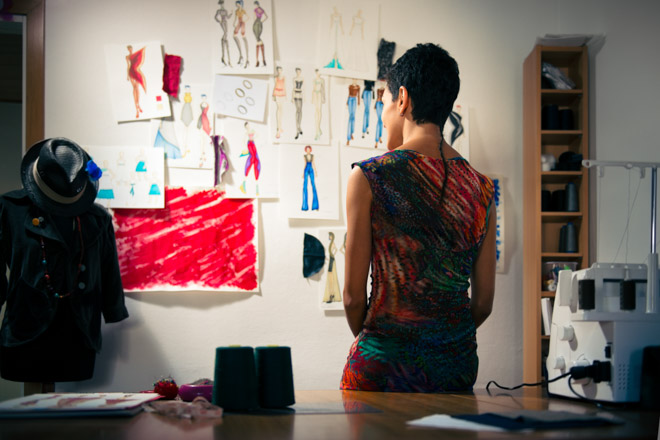 Female fashion designer contemplating drawings in studio