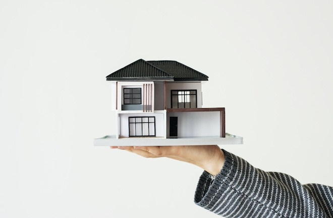 real estate house model in person's hand