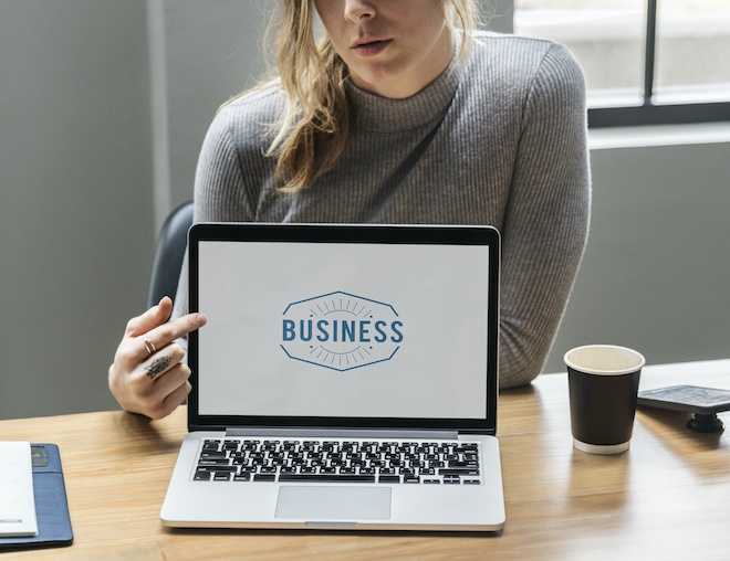 woman pointing at screen with her business logo on it