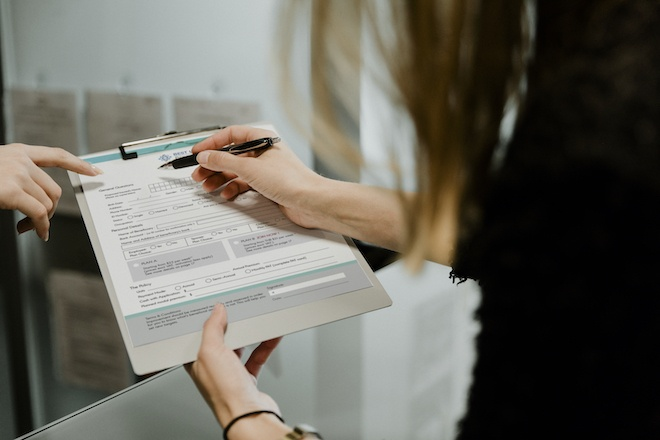woman filling out form on clipboard