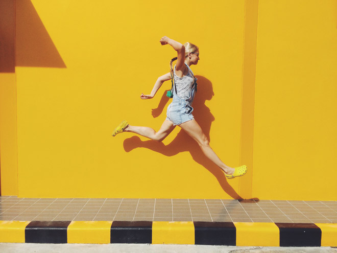 woman jumping on sidewalk with yellow background