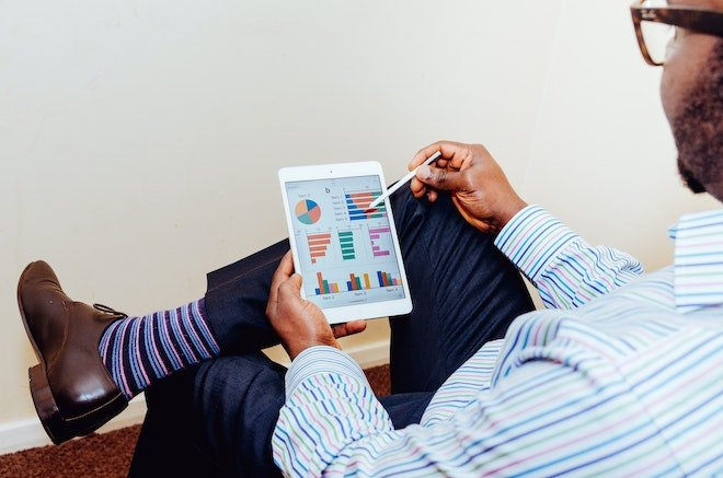man looking at marketing sales data on tablet