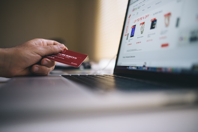 person holding credit card shopping online at laptop
