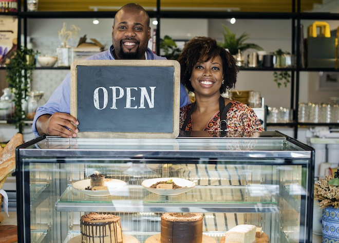 proud business owners behind bakery display case