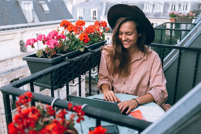 woman working at laptop on balcony