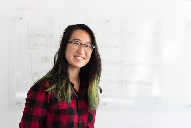 woman posing in front of white board