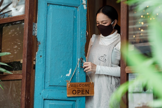 woman with mask putting out open sign on business