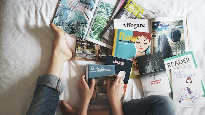 woman sitting on bed with books and magazines