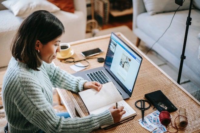 woman writing in planner near laptop