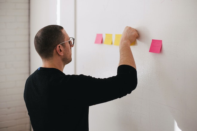 man with sticky notes on wall
