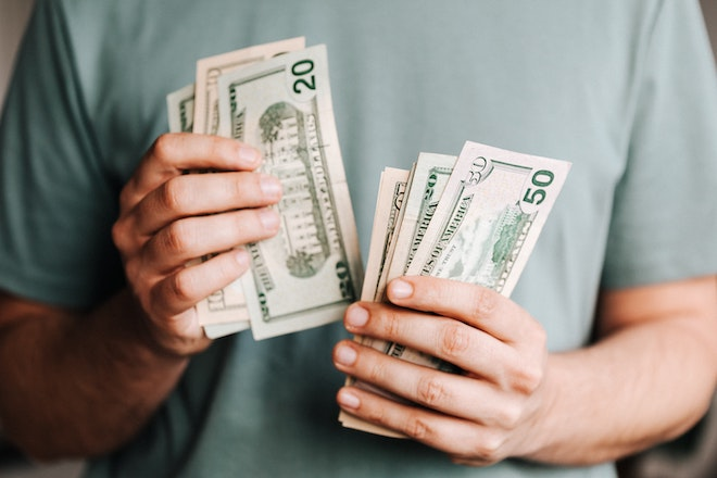 holding stacks of money