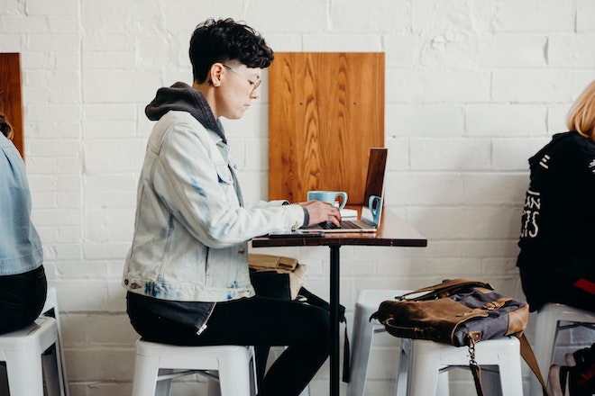 person working at laptop in coffee shop