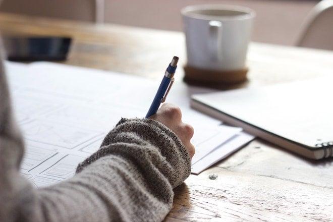 person writing on paper near coffee mug
