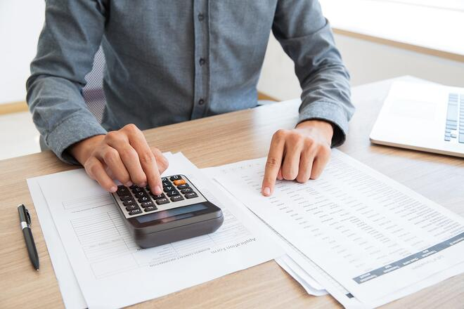 man using calculator to determine taxes