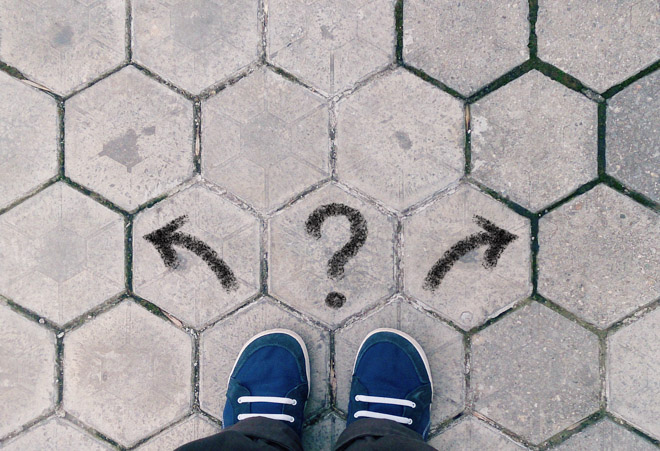 Top view of blue shoes on tiled pavement with question mark and two arrows