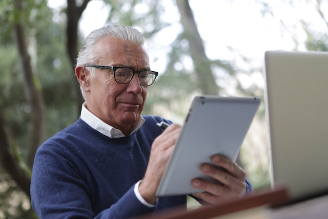 man in blue sweater holding tablet