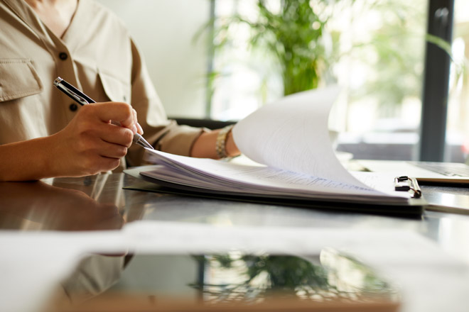 Close-up of manager sitting at the table holding pen and making notes in documents she doing paper work at office