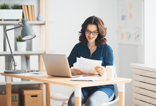woman working on DBA paperwork on laptop