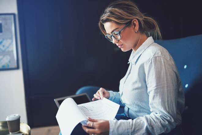 Young businesswoman sitting on a sofa at home reading through paperwork and using a laptop