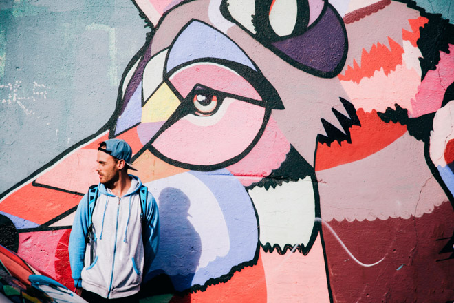 Young man standing in front of colorful mural of a wolf