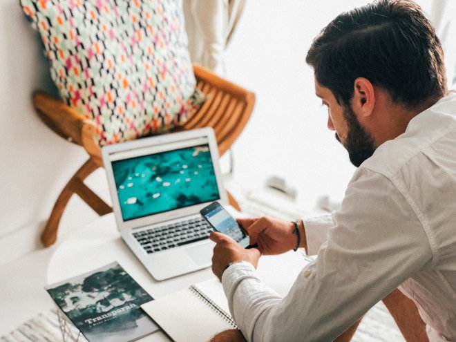 man working on laptop and smartphone from home during pandemic