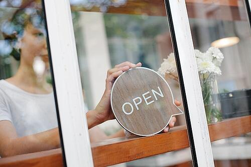 woman putting open sign in business window